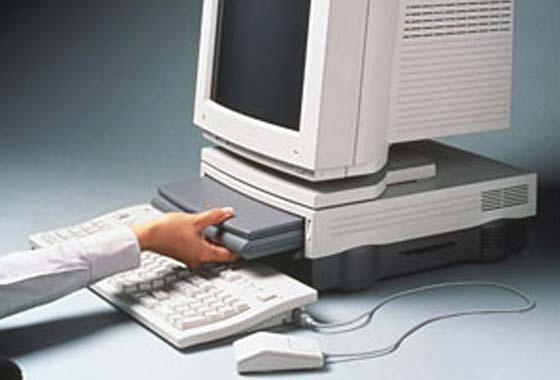A PowerBook Duo 230 being inserted into a Duo Dock